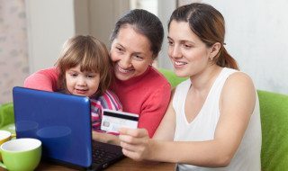 Family of three generations paying by credit card in internet st